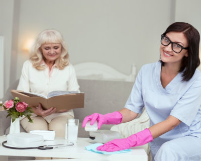 senior women reading book while cheerful caregiver cleaning the house