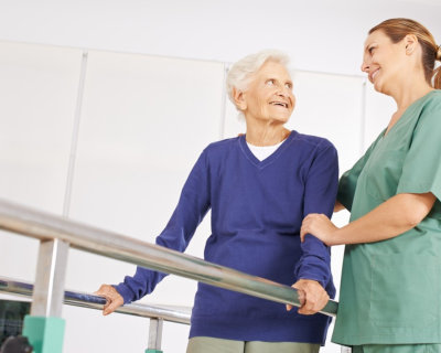woman helping senior woman to walk