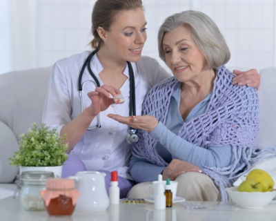 nurse giving medicine to senior woman