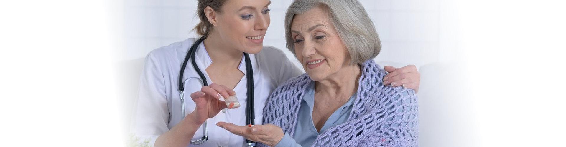 nurse giving medicine to senior woman